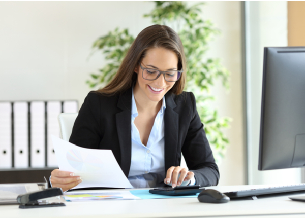 AFG - Woman wearing suit working using a calculator in a desk at office
