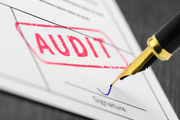 Audit stamped on a document with a pen signing on signature section