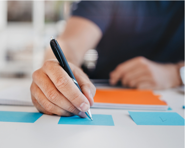 Business man writing on an adhesive note at table in office