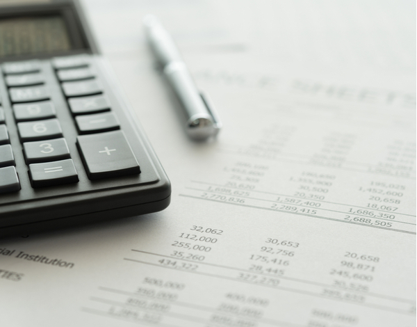 Calculator with accounting report and financial statement on desk