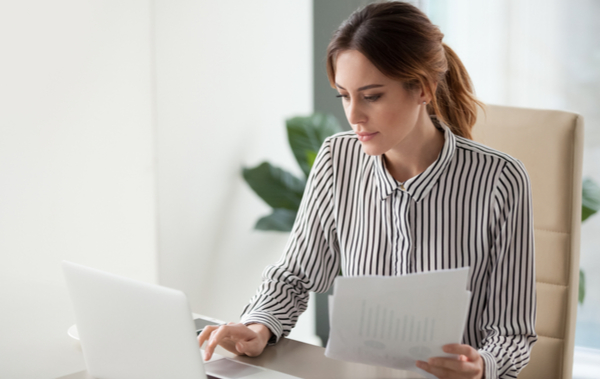Serious focused businesswoman typing on laptop holding papers