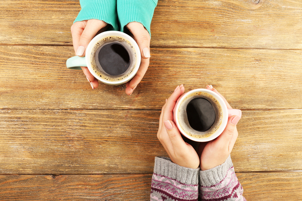Hands of two ladies holding a cup of coffee