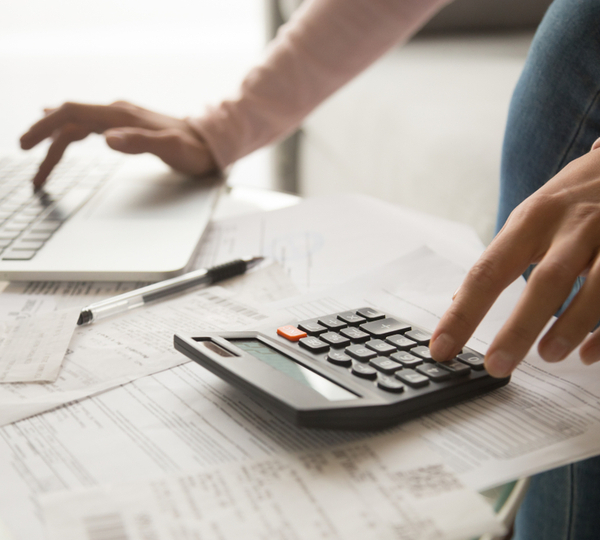 Hand of a woman using calculator and laptop with bills on the table