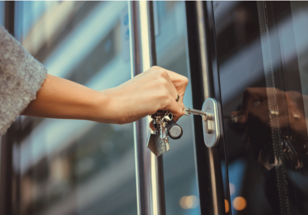 woman using a key in a locked door