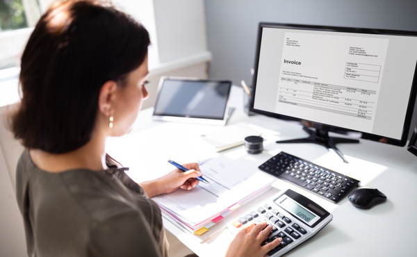 Woman calculating task at office desk