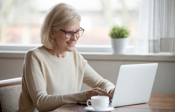 Happy aged woman in glasses working at laptop