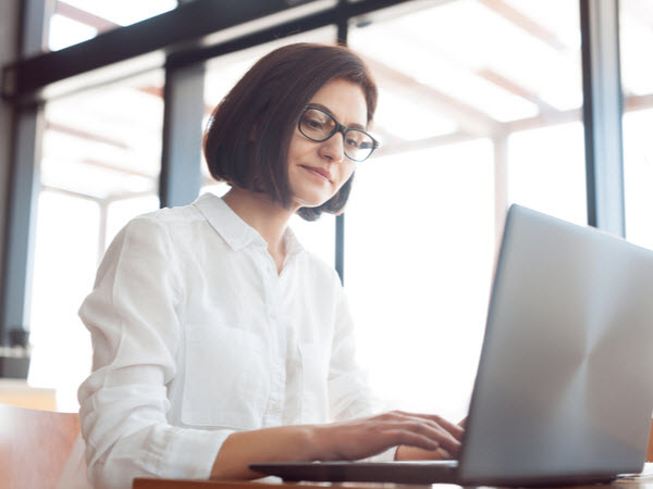 Woman in in glasses sitting inside and working with laptop