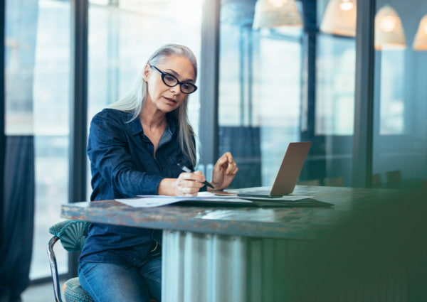 Woman sitting at table in office and reading few paper work
