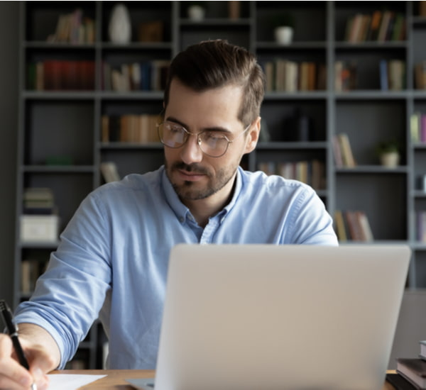 Businessman wearing glasses writing financial report