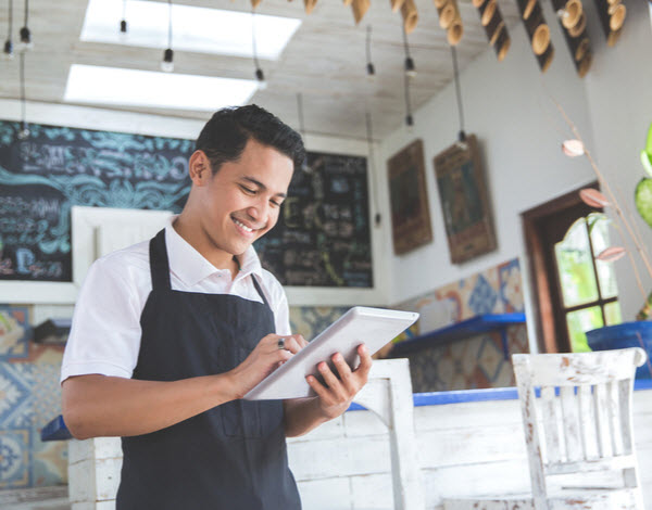 Happy young male cafe owner using tablet