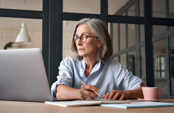 Adult woman holding a pen while looking at her laptop