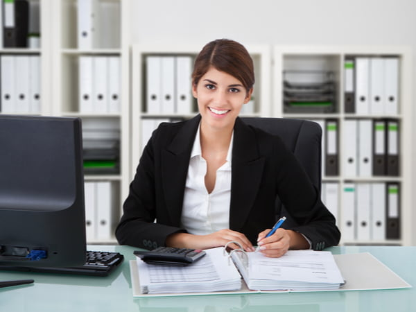 Female accountant writing on documents at desk in office
