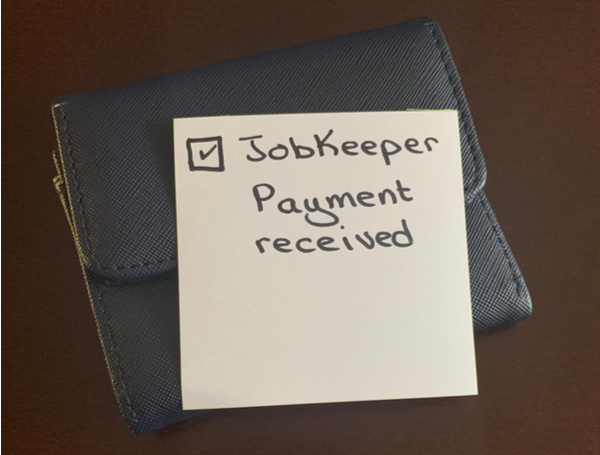 A handwritten note on a blue wallet indicating the JobKeeper Payment has been received