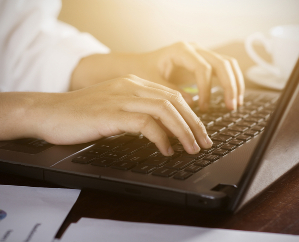 Woman sitting at desk and working on laptop computer close up