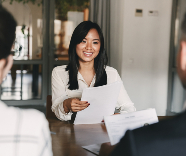 woman smiling and holding resume