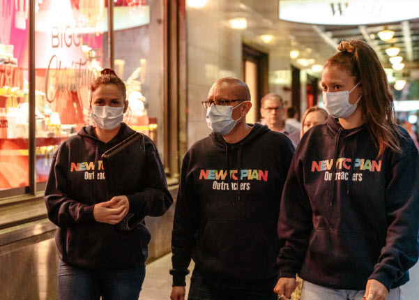 People wearing masks and Newtopian outreacher jacket while walking