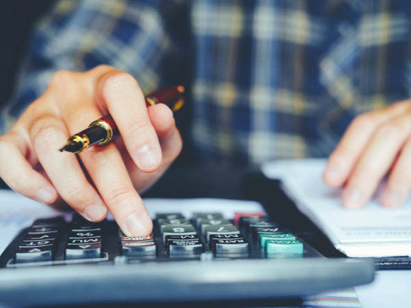 Hand of a man holding a pen while using a calculator in computing