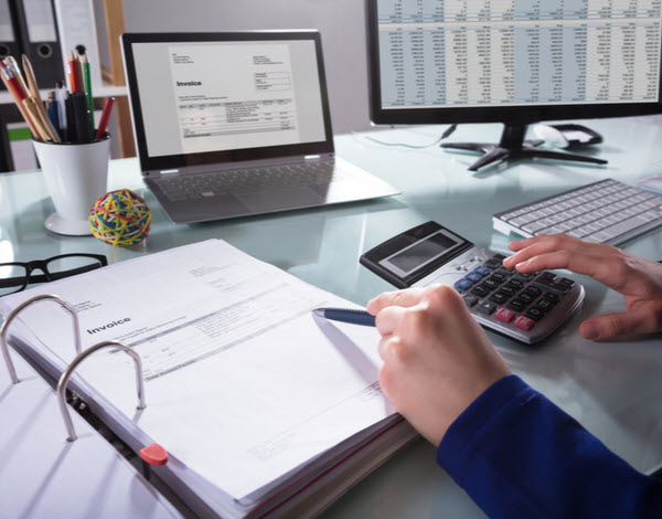 Hand of a person calculating the invoice in the ledger