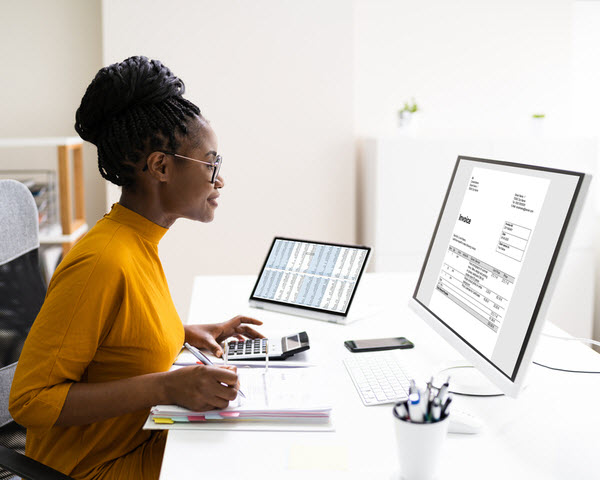Professional woman checking the invoice from her computer while writing on a paper with a calculator beside her