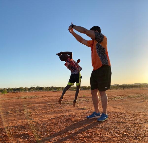 Man playing with Aboriginal kid