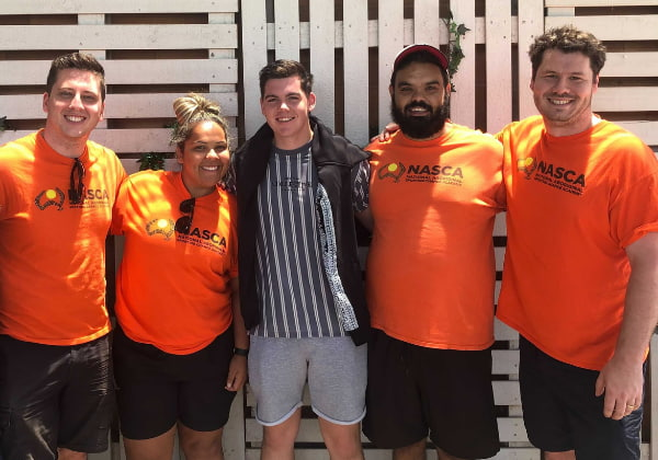 A group of happy people wearing orange shirt