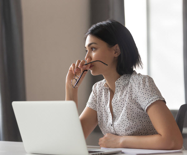 Worried woman thinking while in front of laptop and holding an eyeglasses