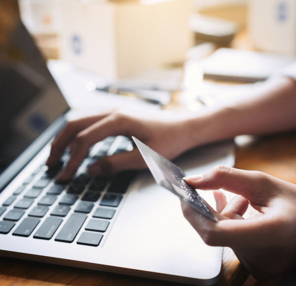 Hands holding credit card for online shopping at home